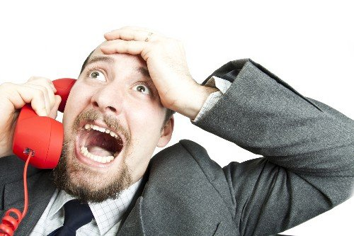 angry businessman screaming into phone