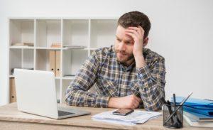Frustrated Business owner sitting at desk