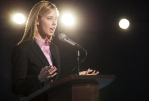 Well dressed young woman giving speech