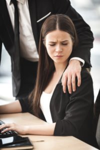 businessman putting hand on assistant - sexual harassment