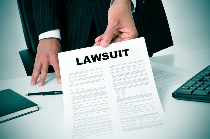 a lawyer delivering a document titled lawsuit