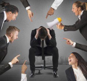 Man in suit being blamed at work