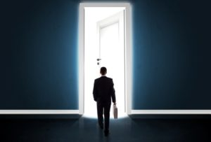 Businessman looking out a bright open door